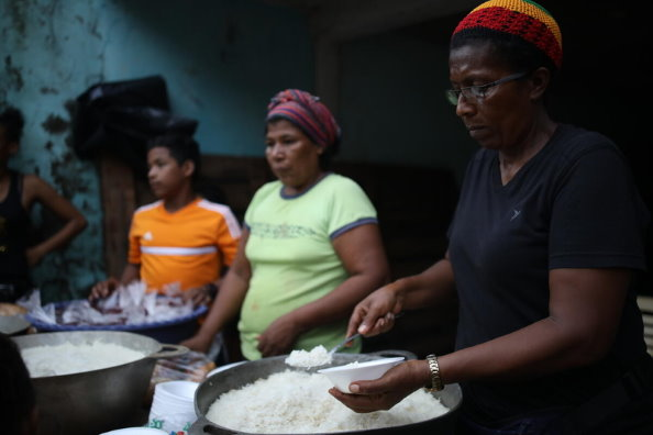WFP/Oscar Duarte, women cooking free meals for the children of the community named Guililandia, who were affected by the Hurricane. Part of the rice she has served to the children was WFP rice.