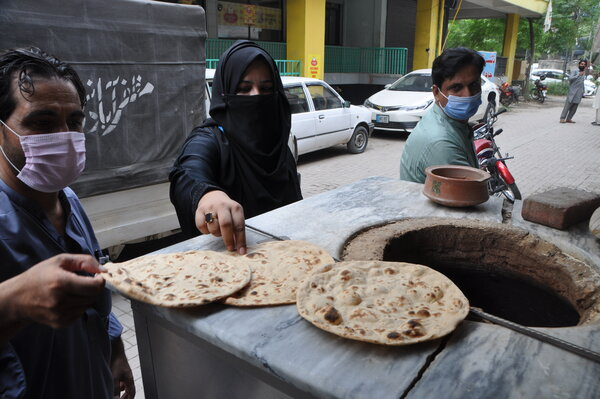 people making and buying chapatis