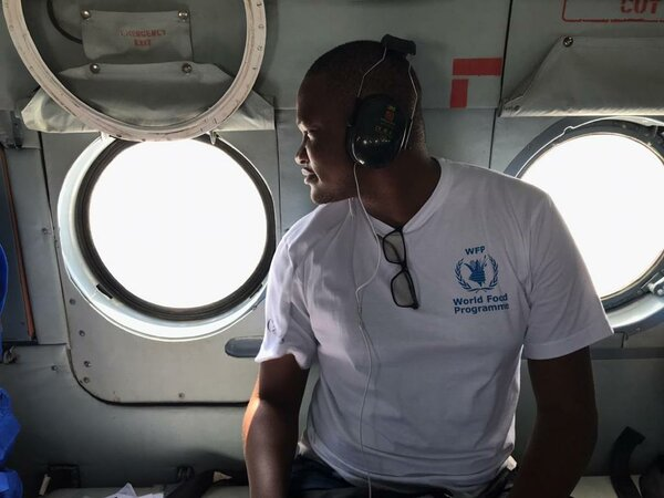 man in white WFP t-shirt looks out of helicopter window