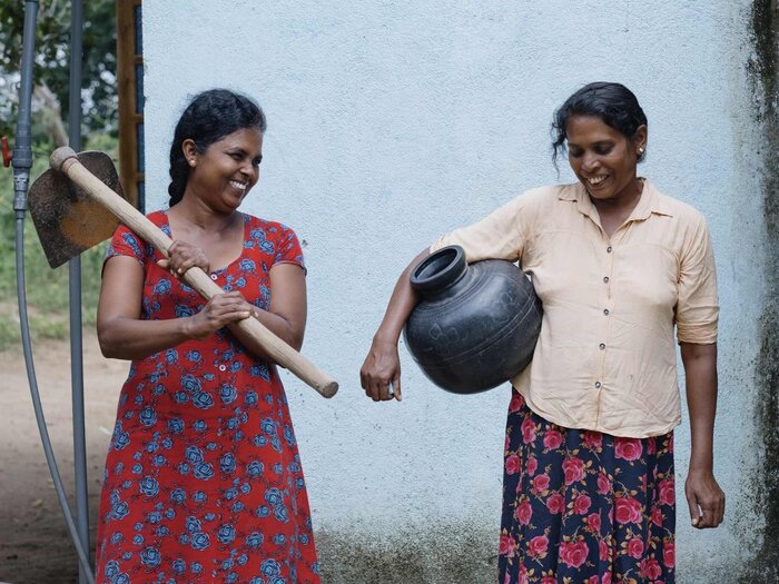 Two women are carrying their equipments to work in the field