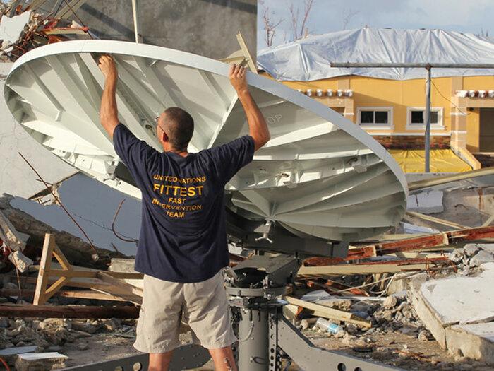 man setting up satellite dish among rubble