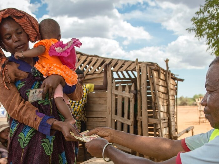 a woman is receiving money when she holds her baby