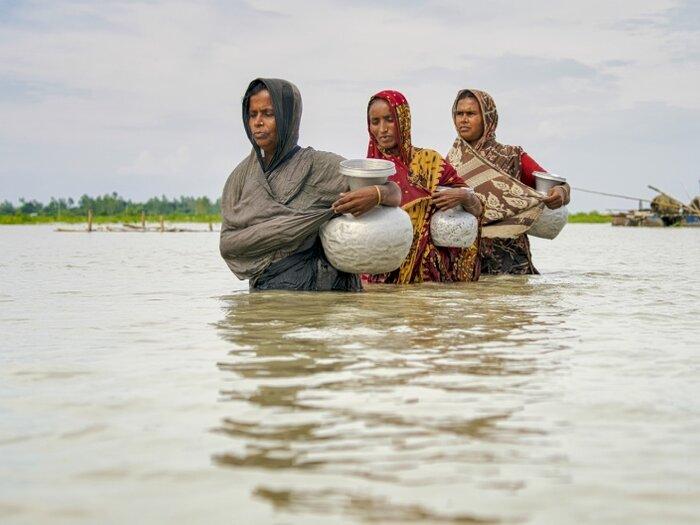 three women walking inside of river