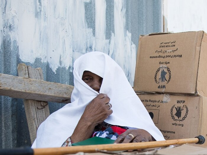 Woman with boxes of WFP aid