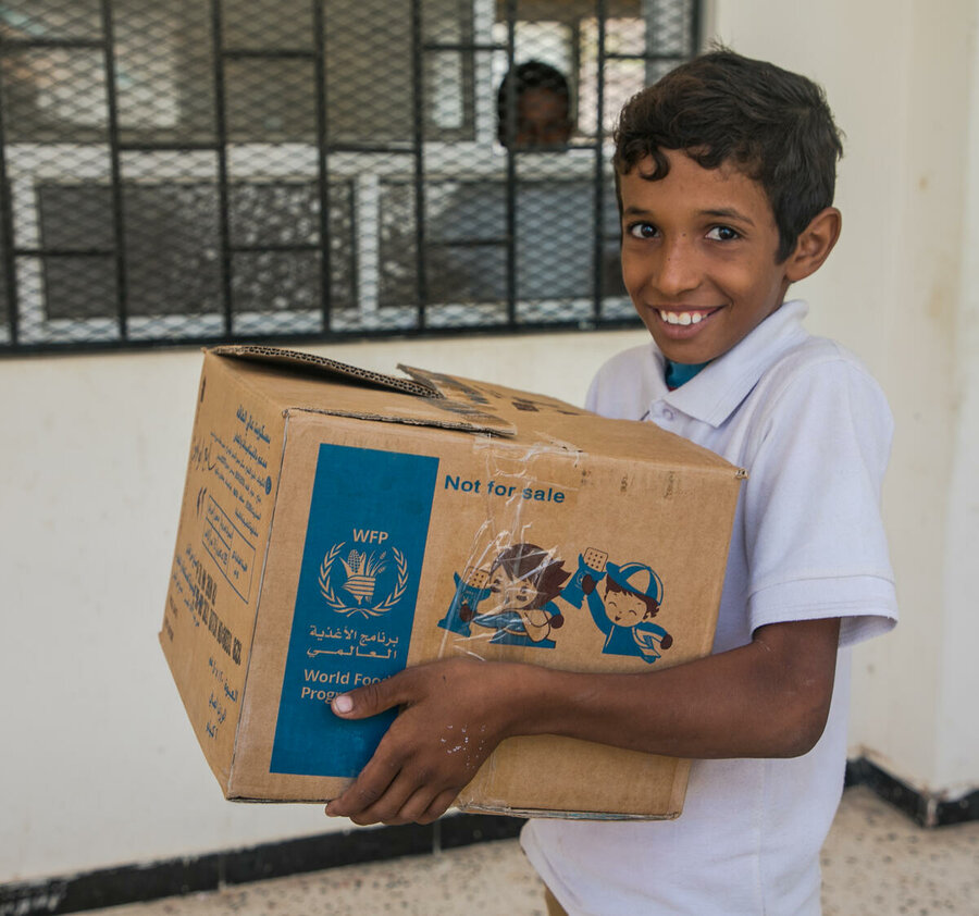 Boy with box of high energy biscuits in Yemen