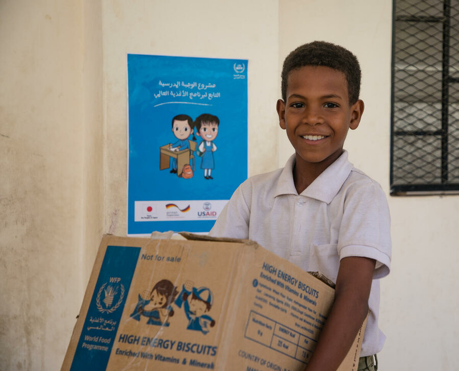 A boy takes delivery of a box of high-energy biscuits at a school in Yemen
