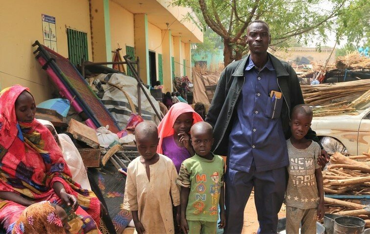 Yahya (R) poses for a picture with his family at their makeshift home at the State Ministry of Welfare in Geneina.