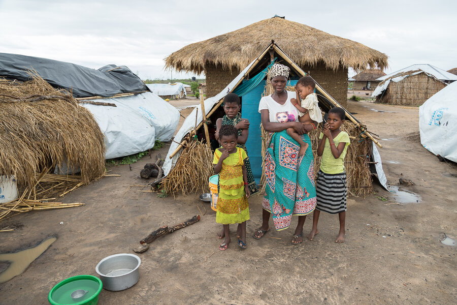 Ancha and her daughters in front of their temporary shelter in 25 de Junho