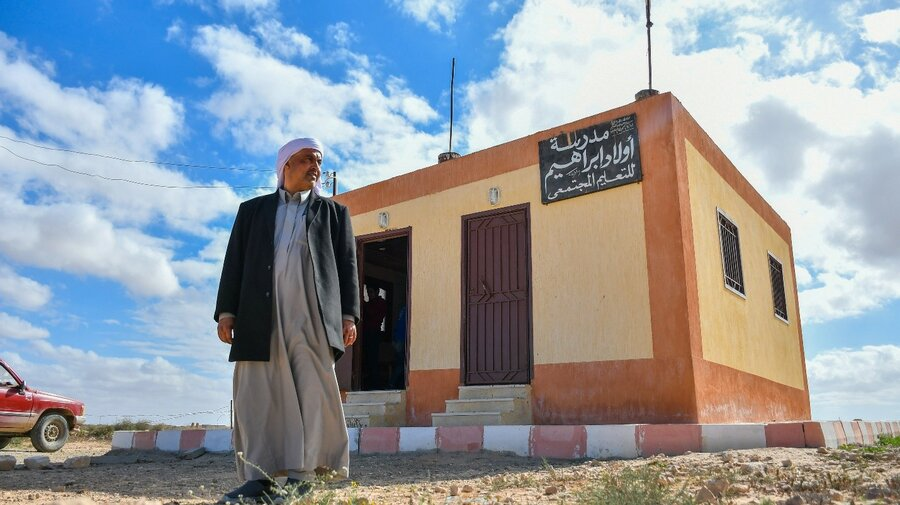Mahmoud Ibrahim stands in front of the school he built himself and now bears his family name