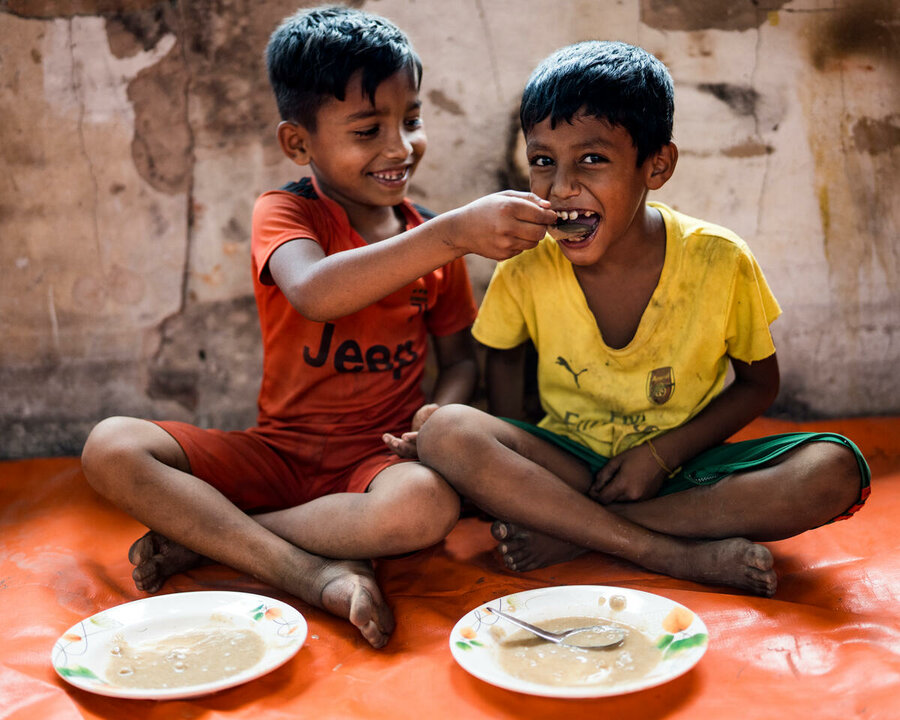 two children are eating their meals