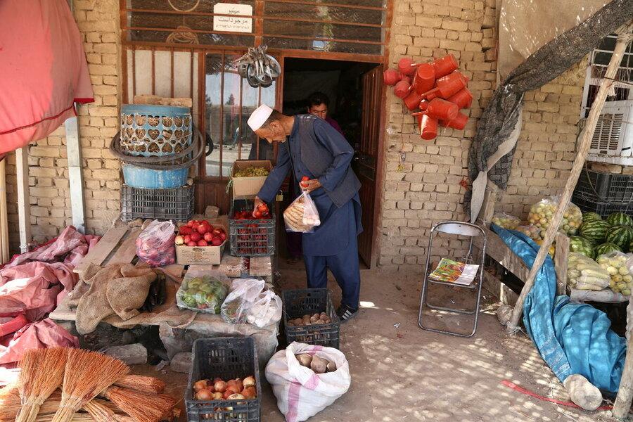 Afghan man choosing food outside shop