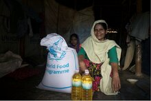 Woman with a bag of WFP food and bottles of vegetable oil