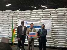 WFP/Adrienne Bolen, Ambassador of the Russian Federation to Zimbabwe, Nikolai V. Krasilnikov hands over a box of wheat procured from Russian funding to Eddie Rowe, WFP Zimbabwe Country Representative & Director and Erasmus Gapara, from Zimbabwe's Ministry of public service, labour and social welfare.