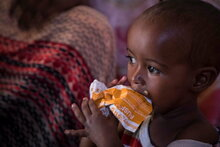 WFP/Marco Frattini, Child eating PlumpySup to treat moderate acute malnutrition (MAM).