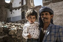Yemeni father holding his daughter in front of a destroyed building