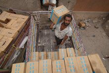 Workers stack food assistance in a warehouse in Lahj on 1 July 2019. Photo credit: WFP/Saleh Baholis